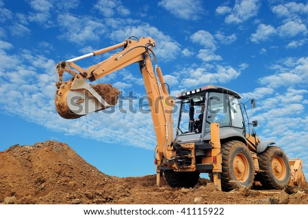 Excavator Loader with rised backhoe standing in sandpit with over cloudscape sky
