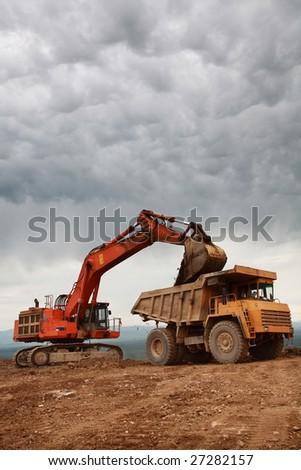 excavator loading big heavy yellow truck - stock photo