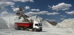 Excavator loading crushed stone into a truck body against the background of stone-crushing equipment, hills of crushed stone and a blue sky with clouds in sunny weather, panorama. Mining industry.