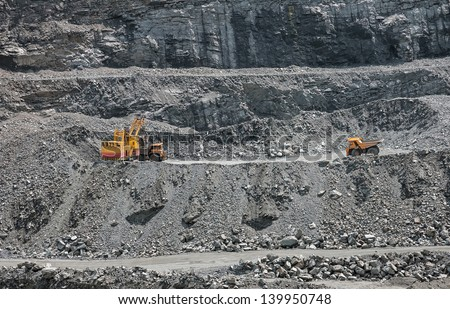 Excavator loading iron ore into the heavy dump truck on the iron ore opencast mine