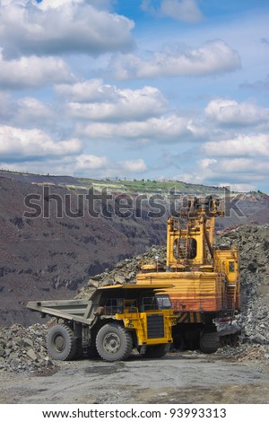 Excavator loading iron ore into the heavy dump truck on the iron ore opencast mining