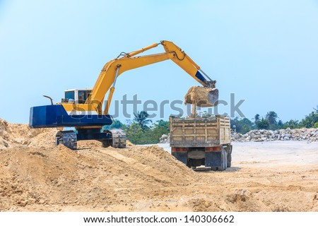excavator loading sand on dumper truck at dolomite mines site