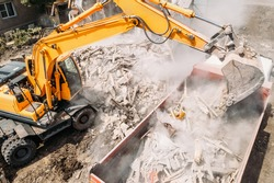 Excavator loads construction waste into truck for removal from construction site. Demolition of dilapidated housing for new development