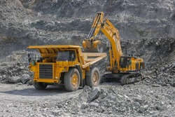 Excavator loads ore into a large mining dump truck. Open pit
