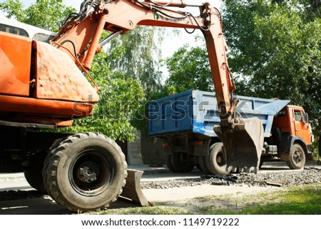 excavator loads the car in the city, repairs roads using heavy equipment, loading of asphalt #1149719222