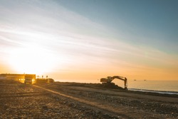 Excavator loads the excavation onto a truck (hydraulic)are heavy construction equipment consisting of an arrow,a bucket and a cabin on a rotating platform.On the beach with the sea and the setting sun