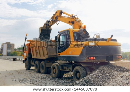 Excavator loads the load of material into the car body. Repair of road structures, coatings #1445037098