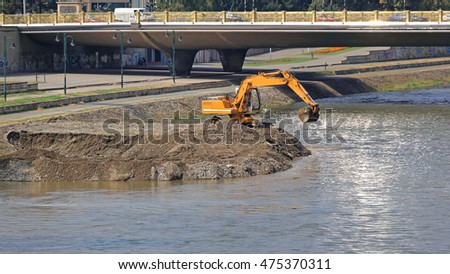 Excavator Machine Digging Levee at River Embankment ストックフォト ©