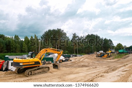 Excavator machine during construction road works and various heavy vehicles in background. Heavy machinery equipment at road construction site. Preparation for construction of  highway