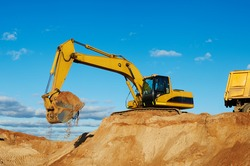 excavator machine loading dumper truck at sand quarry