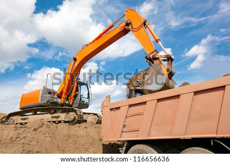 Excavator machine loading soil or sand into truck body