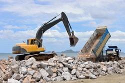 Excavator machine moves stone with raised bucket to truck