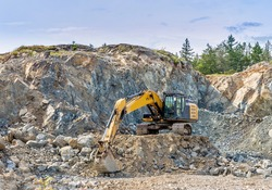 Excavator machine moving earth and stone in a large rocky pit as part of a construction project