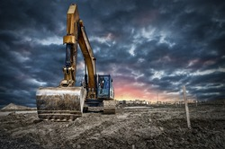 Excavator machinery at construction site, sunset in background.