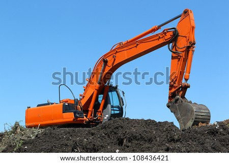 excavator on a compost heap against a blue sky
