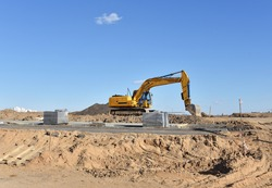 Excavator on earthmoving at construction site. Backhoe digs sand on blue sky background. Construction machinery for excavation, loading, lifting and groundwork on job sites.