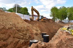 Excavator on earthwork during the laying of pipes of the heating system to a new residential building at the construction site. Laying concrete sewer wells, rings and manholes in ground.