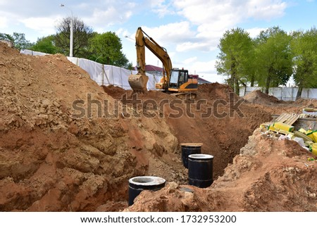 Excavator on earthwork during the laying of pipes of the heating system to a new residential building at the construction site. Laying concrete sewer wells, rings and manholes in ground.  Stock photo ©