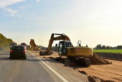 Excavator On Earthworks and Road Construction in City. Temporary Traffic Regulation from carrying out road works or activity on the public highway. Roadway Work Zone Safety. Out of focus, motion blur