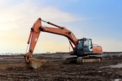 Excavator on earthworks at construction site. Backhoe on earthmoving and foundation work. Heavy machinery and equipment.