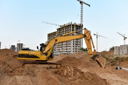 Excavator on earthworks at construction site. Backhoe on foundation work and road construction. Tower cranes in action on blue sky background. Heavy machinery and construction equipment