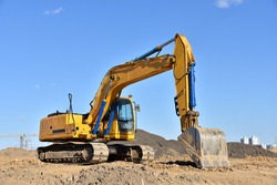 Excavator on earthworks at construction site. Backhoe on foundation work and road construction. Heavy machinery and construction equipment