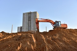 Excavator on earthworks at construction site. Backhoe on foundation work and road construction. Heavy machinery and construction equipment. Excavator under building