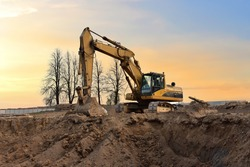 Excavator on earthworks at construction site on sunset background. Digging a foundation pit and a trench for laying sewer pipes.  Renovation and construction of a residential multi-storey building