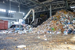 Excavator on primary sorting of garbage at waste processing plant. Separate garbage collection. Recycling and storage of waste for further disposal.
