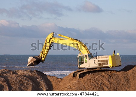 Excavator on the beach working with sand