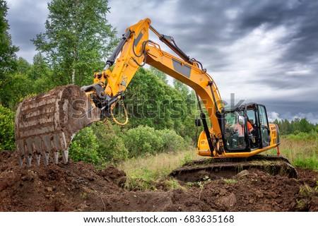 Excavator on the gas pipeline performs excavation work