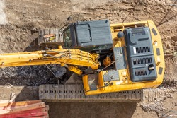 Excavator on the ground of a construction site with a raised bucket, top aerial view