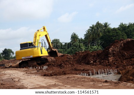Excavator on working site, moving earth by its bucket