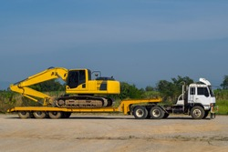 Excavator or Backhoe on the truck hauls stopping in site construction. Heavy transport truck