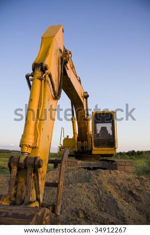 Excavator overlooking farmland