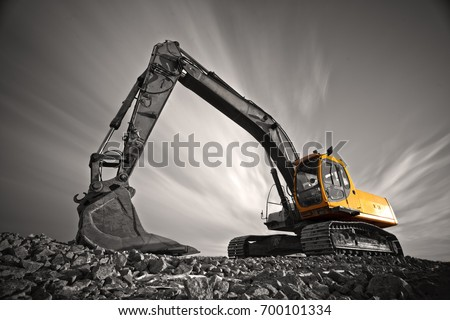 Excavator parked on stone ground against dramatic sky