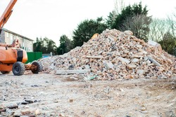 Excavator removes construction waste after building demolition. Building rubble, bricks, stones. Junk, Garbage piled up. Street scene. Recycling industry, rubbish removal, and collection service