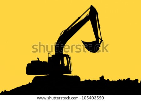 Excavator standing in a ground with raised bucket over cloudscape sky
