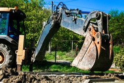 Excavator used for pipe laying works and house foundation. Digging a trench using a dump truck. Pipeline earthworks at the construction site. Digger backhoe filled with earth.
