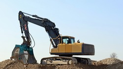 Excavator with a large screening bucket on a gravel ground.