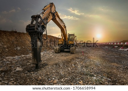 Excavator with hydraulic hammer on road construction works
