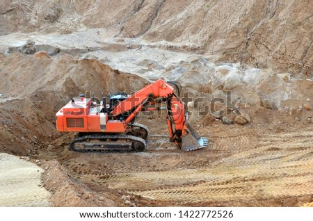 Excavator with large bucket in working in a opencast quarry.  Mining quarry for the production of crushed stone, sand and gravel for use in the construction industry - Image #1422772526