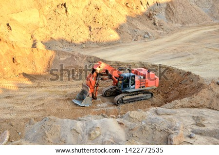 Excavator with large bucket in working in a opencast quarry.  Mining quarry for the production of crushed stone, sand and gravel for use in the construction industry - Image #1422772535