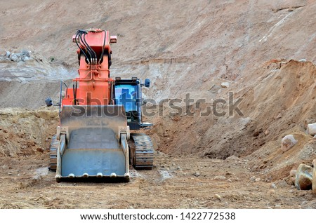 Excavator with large bucket in working in a opencast quarry.  Mining quarry for the production of crushed stone, sand and gravel for use in the construction industry - Image #1422772538