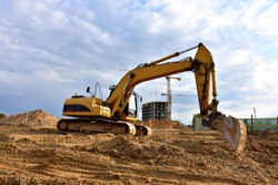 Excavator working at construction site. Backhoe during earthworks. Digging ground for the foundation and for laying sewer pipes district heating. Earth-moving heavy equipment