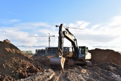 Excavator working at construction site on earthworks. Backhoe digging building foundation. Paving out sewer line. Heavy machinery for road work, excavating, loading, lifting and hauling of cargo