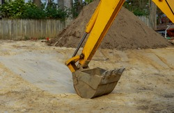 Excavator working bucket moving for foundation at construction on earthworks