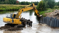 Excavator working in the small forest river, excavator bucket. Construction of the new bridge, bridge construction engineering