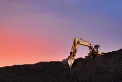 Excavator working on earthmoving at open pit mining on sunset background. Backhoe digs sand and gravel in quarry. Heavy construction equipment during excavation at construction site