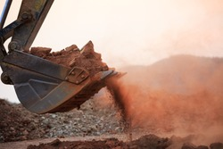 Excavator working with red soil and dusty